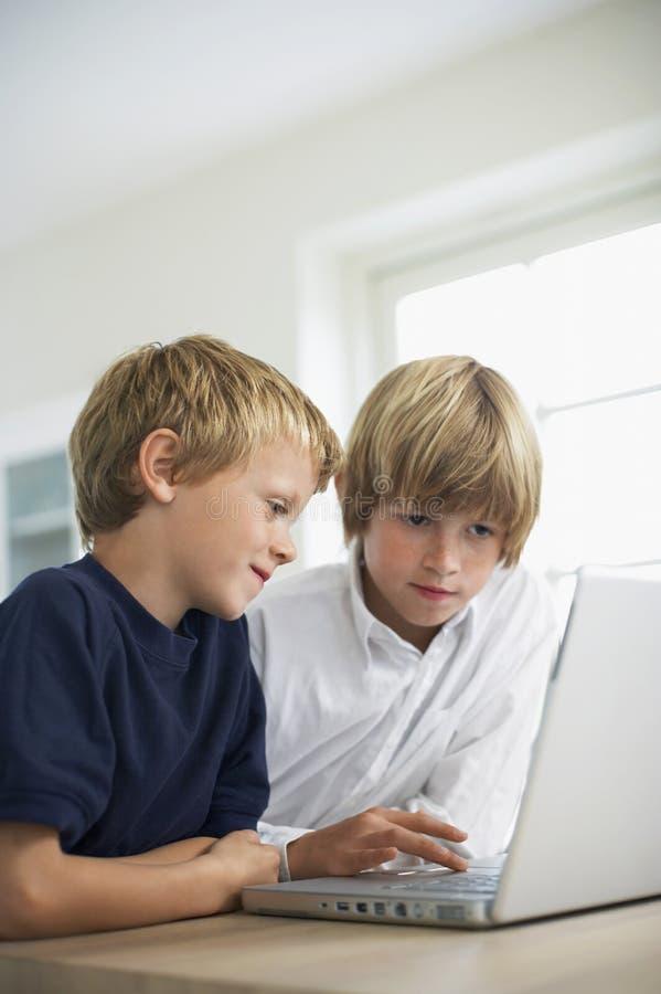 Frères à l'aide de l'ordinateur portable sur le Tableau image libre de droits