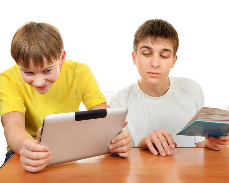 Frères avec un livre et une Tablette photo stock