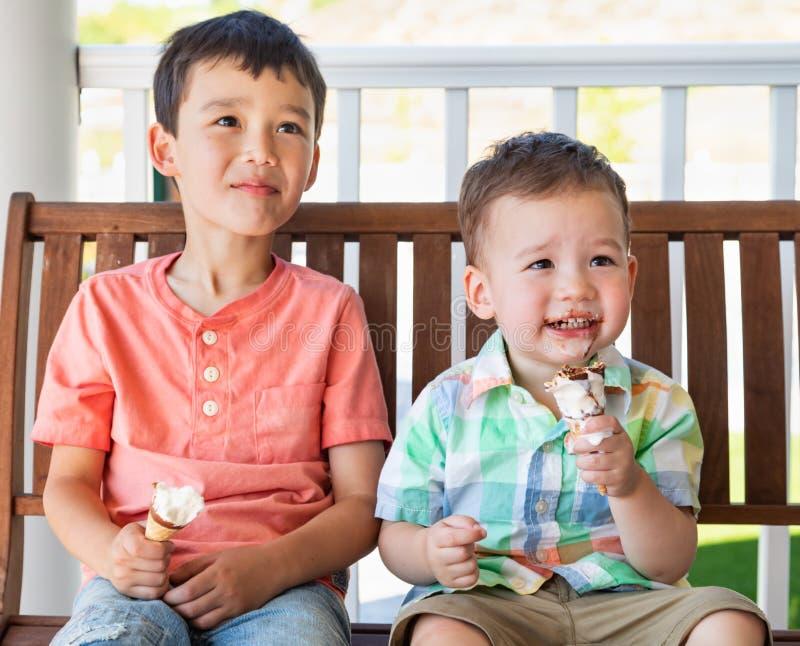Frères caucasiens chinois de jeune métis mangeant des cornets de crème glacée image libre de droits
