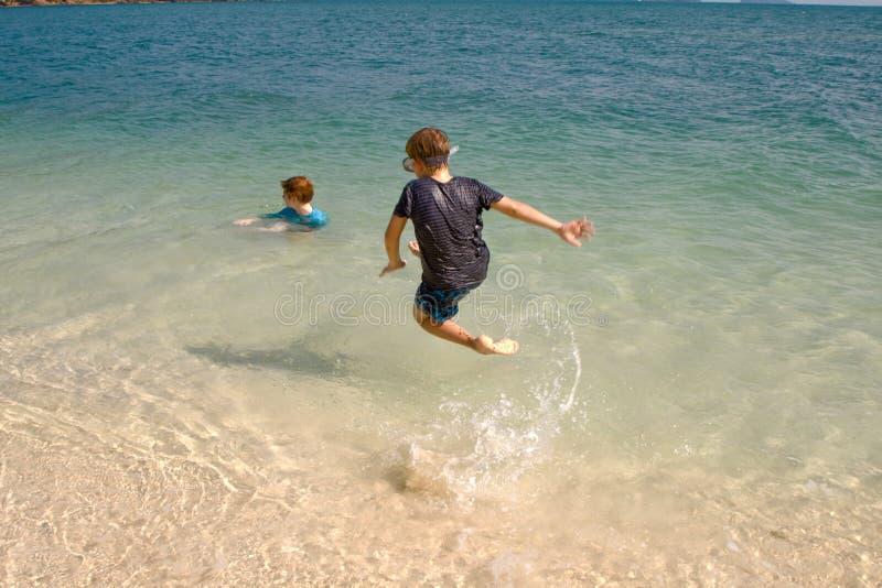 Frères jouant ensemble dans le bel océan photo libre de droits