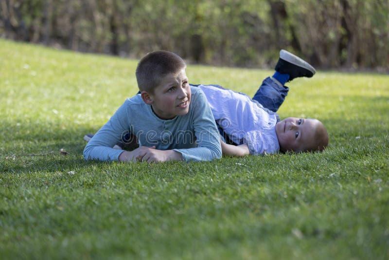 Frères jouant sur l'herbe en été photo stock