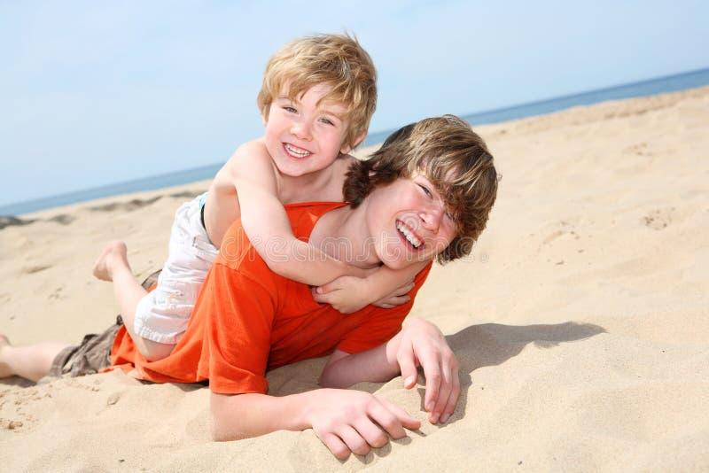 Frères jouant sur la plage photo stock