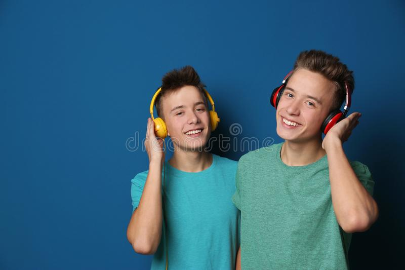 Frères jumeaux adolescents avec des écouteurs photos stock