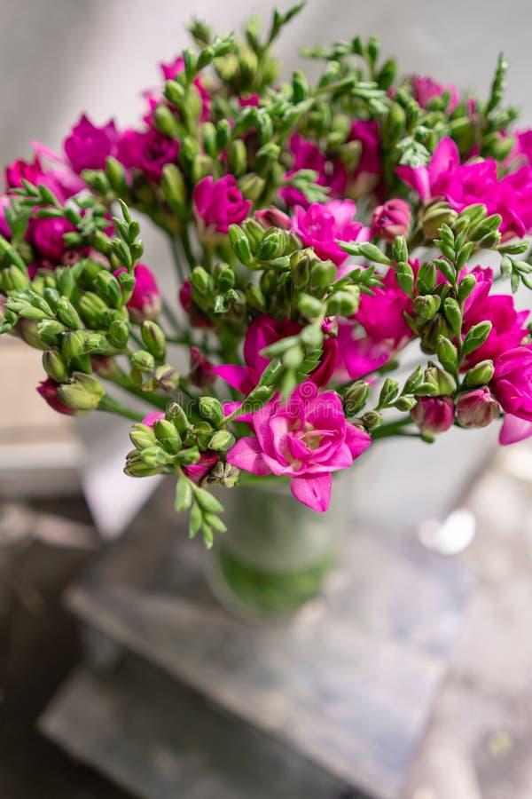 A frésia cor-de-rosa brilhante floresce no vaso de vidro na tabela de madeira Ramalhete bonito do verão Arranjo com flores da mis fotos de stock