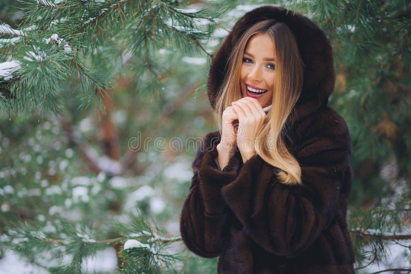 Frío de la muchacha en bosque del invierno foto de archivo