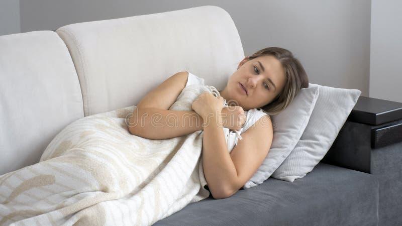 Frío de sensación de la mujer morena enferma joven mientras que miente debajo de la manta en el sofá imagenes de archivo