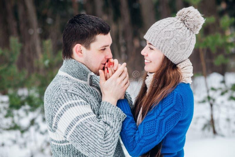 Frío que va de los pares abrigado en invierno al aire libre Hombre que lleva a cabo las manos su novia en parque del invierno foto de archivo