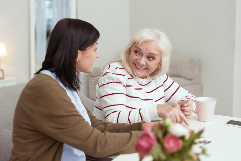 Fröhliche ältere Frauen- und Pflegekraftunterhaltung stockfoto