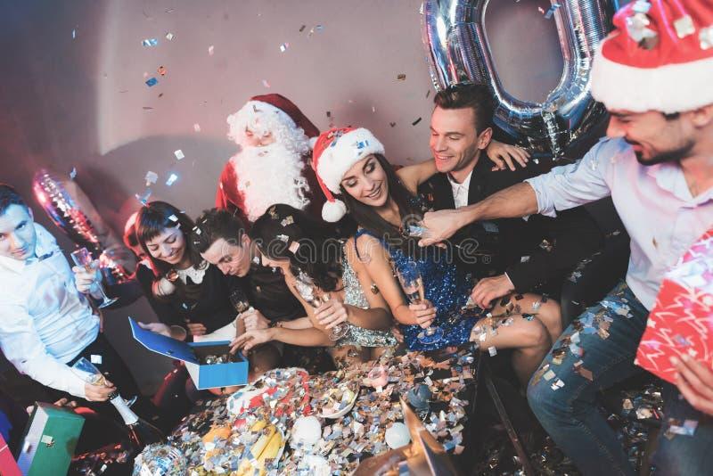 Fröhliche Firma an der neues Jahr ` s Partei Leutegetränkchampagner- und -austauschgeschenke stockbild
