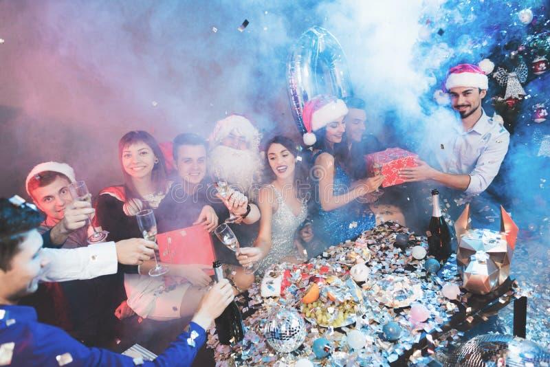 Fröhliche Firma an der neues Jahr ` s Partei Leutegetränkchampagner- und -austauschgeschenke stockbilder