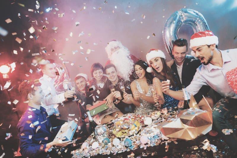 Fröhliche Firma an der neues Jahr ` s Partei Leutegetränkchampagner- und -austauschgeschenke lizenzfreie stockfotografie