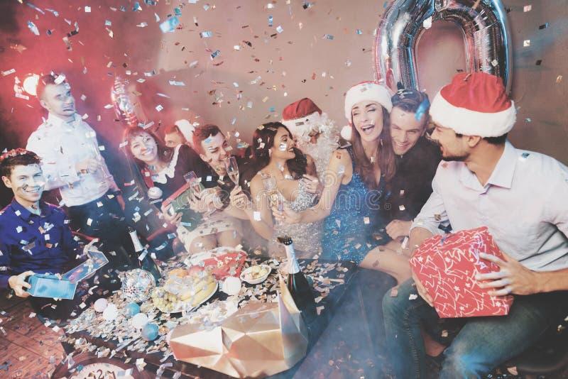 Fröhliche Firma an der neues Jahr ` s Partei Leutegetränkchampagner- und -austauschgeschenke lizenzfreie stockfotos