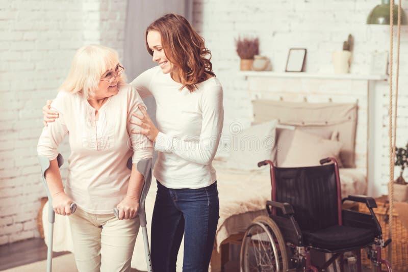 Fröhliche junge Frau, die zu Hause arbeitsunfähiger alter Dame hilft lizenzfreie stockfotos