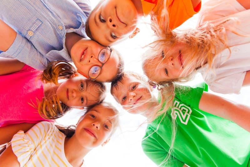 Fröhliche Kinder, die in einem Kreis stehen, der ihre Köpfe berührt lizenzfreie stockfotografie