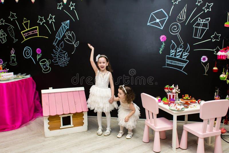 Fröhliche kleine Mädchen auf einem Kinderurlaub im Hintergrund eines schwarzen Brettes für Glückwünsche und Dekorationen lizenzfreies stockfoto