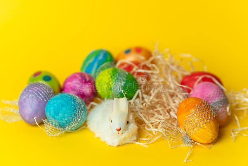 Fröhliche Ostern - bunt, handgemalte, Pastell-Ostereier auf einem Gelb, Frühlingshintergrund lizenzfreie stockfotografie