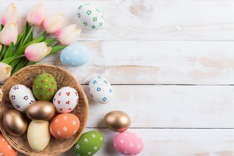 Fröhliche Ostern! Bunt von Ostereiern im Nest mit rosa Tulpenblume und in der Feder auf hölzernem Hintergrund lizenzfreies stockfoto