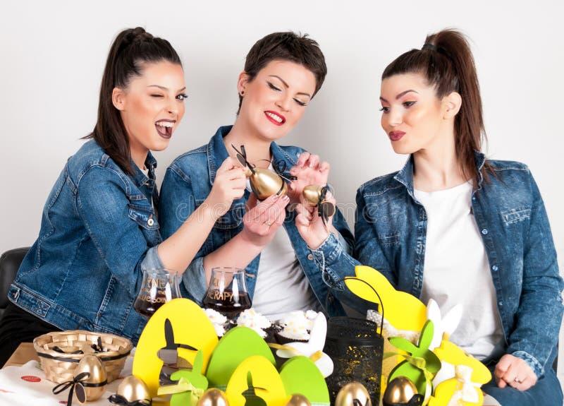 Fröhliche Ostern Die Mädchen, die mit Malereieiern bei Ostern spielen, verzieren Tabelle lizenzfreie stockfotografie