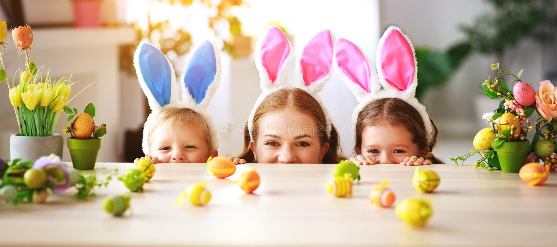 Fröhliche Ostern! Familienmutter und -kinder mit den Ohrhasen, die zum Feiertag fertig werden stockfotos