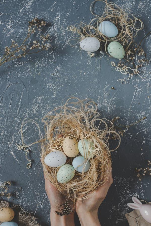 Fröhliche Ostern Hände, die Ostereier im Nest mit Ostern-Dekoration, Draufsicht halten lizenzfreie stockfotografie