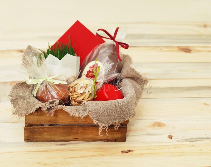 Fröhliche Ostern, Holzkiste mit Geschenken, Kerzen-Ei, Ostern-Kuchen, Schokoladen und grünem Gras Kopieren Sie Platz lizenzfreies stockbild