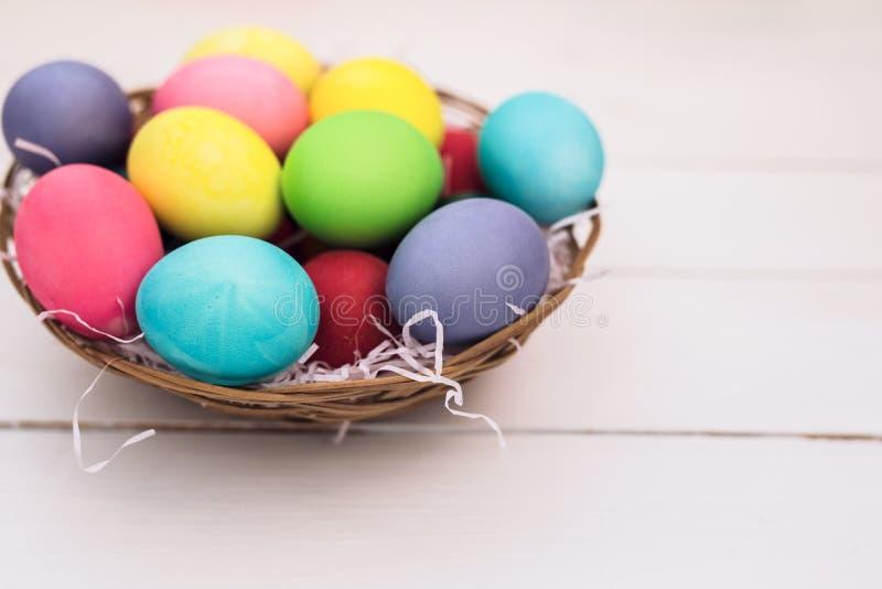 Fröhliche Ostern mit bunten Pastell-Ostereiern auf hölzernem Hintergrund stockfotografie