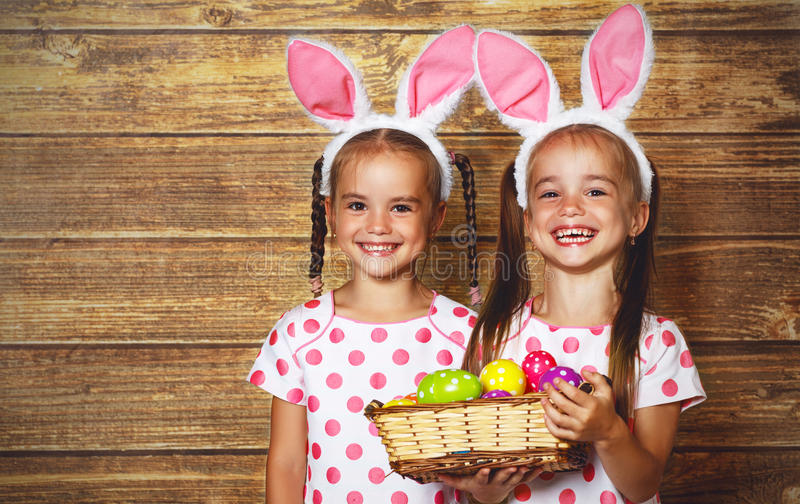Fröhliche Ostern! nette Zwillingsmädchenschwestern gekleidet als Kaninchen mit e stockbilder