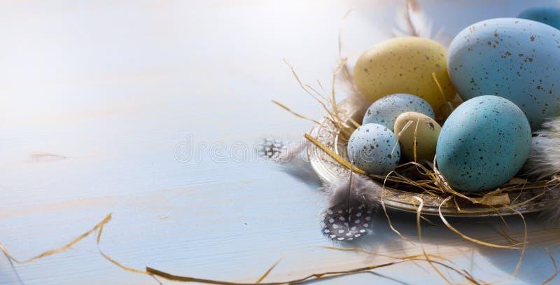 Fröhliche Ostern; Ostereier auf blauem Tabellenhintergrund Feiertage konkurrieren stockbild