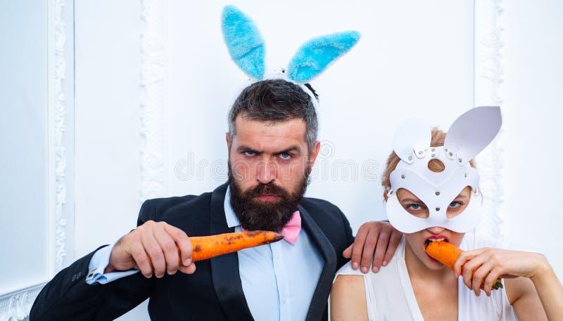 Fröhliche Ostern und lustiger Ostern-Tag Überraschte tragende Häschenohren der Häschenpaare und Karotte essen Lächeln Ostern stockbild