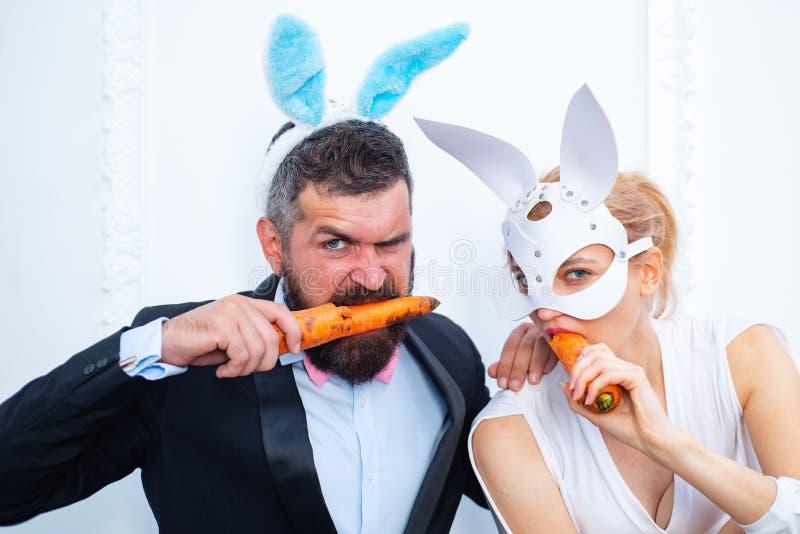 Fröhliche Ostern und lustiger Ostern-Tag Häschenohrkostüm Überraschte tragende Häschenohren der Häschenpaare und Karotte essen lizenzfreie stockfotos