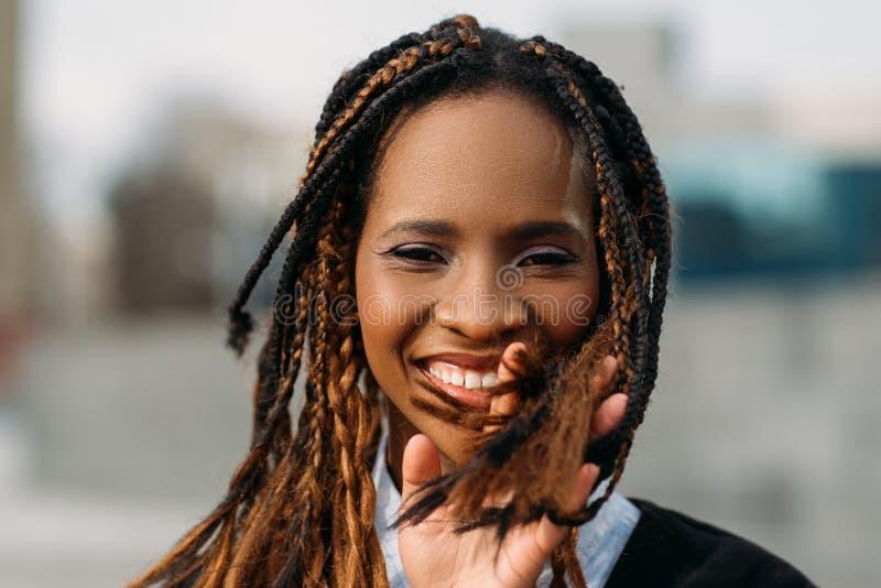 Fröhliche schwarze Frau draußen Stilvolles Baumuster stockfotografie