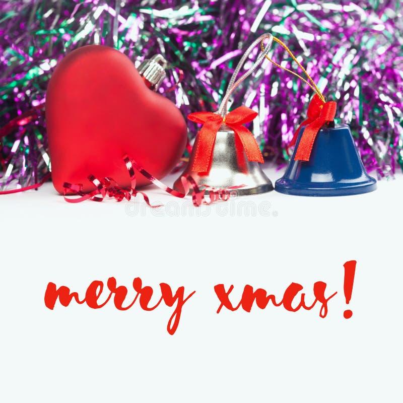 Fröhliche Weihnachtskarte mit rotem Herzen, Klingelglocken und Bändern Weißer Hintergrund stockfotos