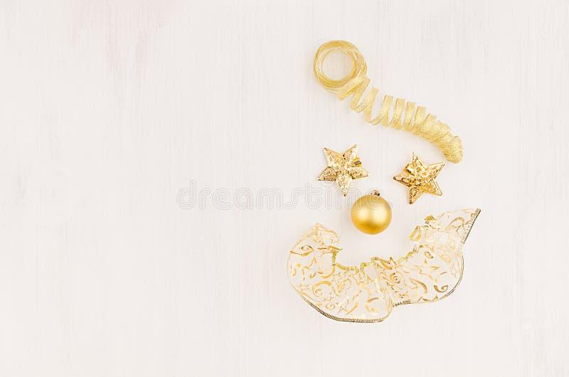Fröhlicher Gesichtsweihnachtsclown von Goldsternen, Lockenbänder auf weichem weißem hölzernem Brett, Draufsicht, Kopienraum lizenzfreie stockfotografie