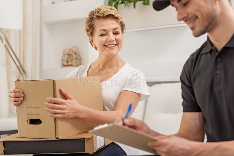 Fröhlicher lächelnder Mann liefert Paket lizenzfreie stockfotografie