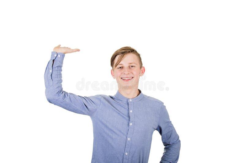 fröhlicher Teenagerjunge hält den Arm hoch, als würde er etwas Unsichtbares in seiner Handpalme versteckt über weißem Hintergrund stockbilder