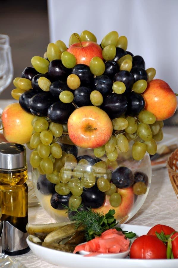 Früchte in einem Vase auf dem Tisch, decorWedding Blumensträuße und Eheringe heiratend, Hochzeit Boutonnieres stockfotos