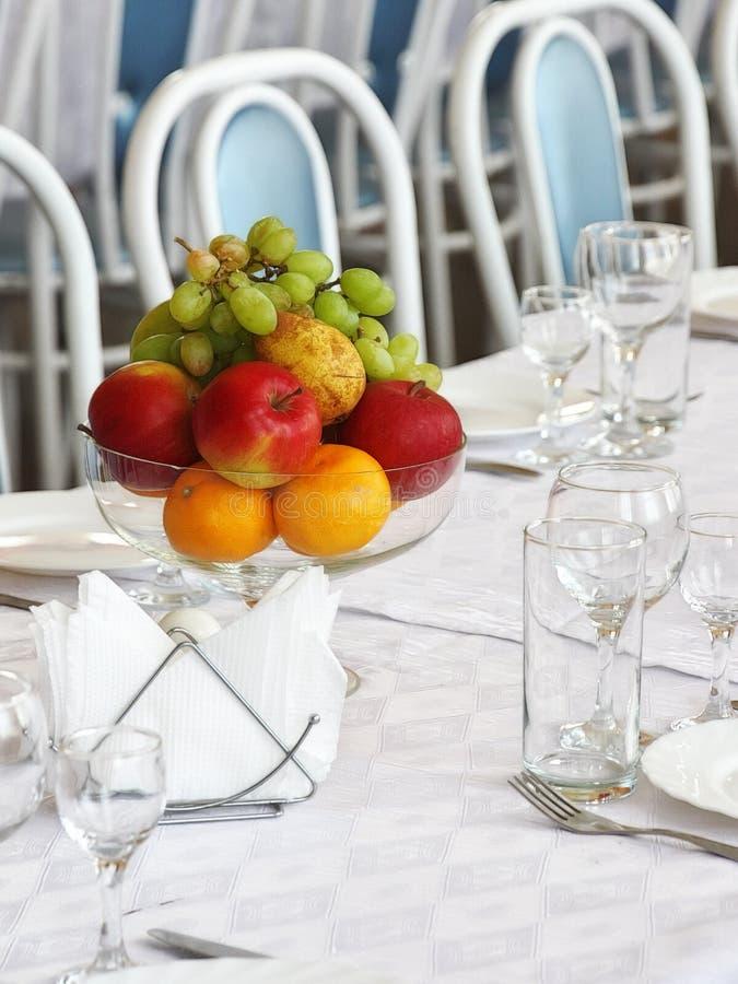 Früchte in einem Vase und in Glaswaren auf dem Tisch stockbilder