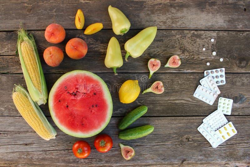 Früchte, Gemüse, Pillen auf hölzernem Hintergrund stockfoto