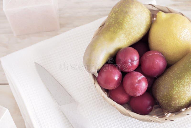 Früchte im Korb in den auf dem Tisch, Birnen und in den Zitronen, zusammen mit den Pflaumen der Server, lizenzfreies stockfoto