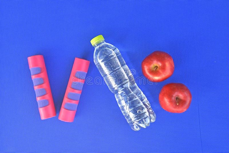 Früchte mit dumbells und Wasserflasche auf blauer Yogamatte stockfotografie