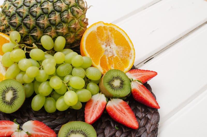 Früchte und Beeren auf einem weißen Holz lizenzfreies stockbild