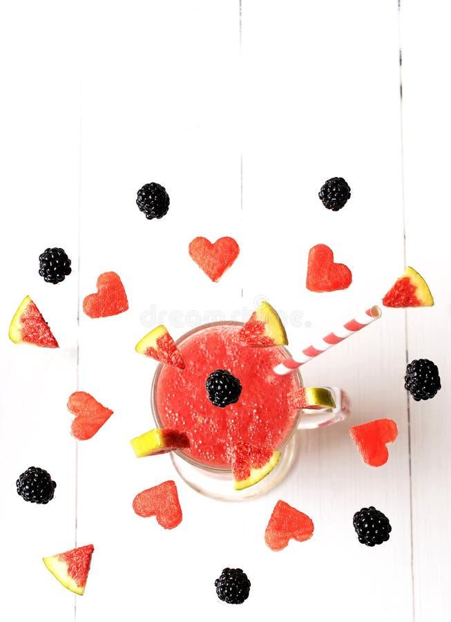 Früchte und Beeren, die in ein Glas fliegen stockfotografie