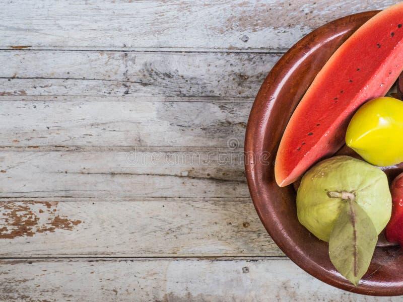 Früchte vergipsen im Behälter gesetzten hölzernen Hintergrund stockfotos