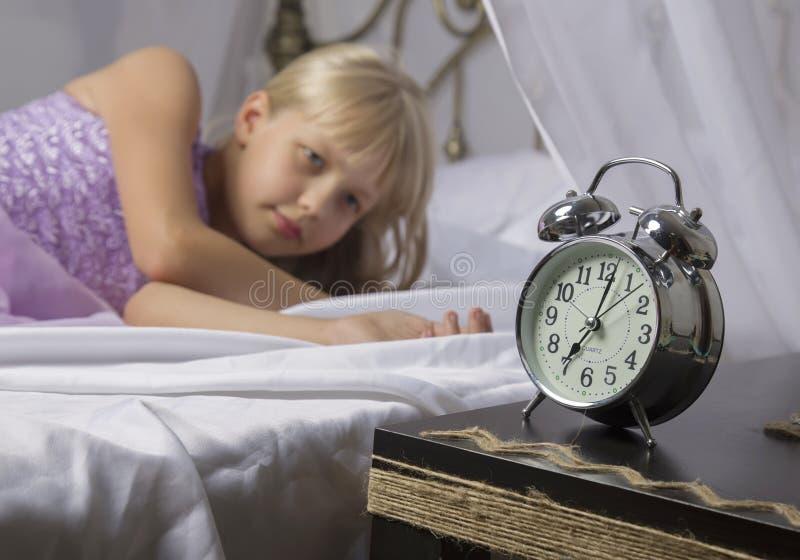 Früh weckend Wachen Sie von einem schlafenden jungen Mädchen auf, das morgens Wecker auf einem Bett stoppt stockfotografie