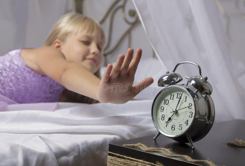 Früh weckend Wachen Sie von einem schlafenden jungen Mädchen auf, das morgens Wecker auf einem Bett stoppt stockbilder