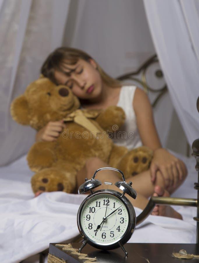 Früh weckend Wecker, der auf Nachttisch steht Wachen Sie von einem schlafenden jungen Mädchen auf, das Teddybären im Bett auf a h stockfotografie