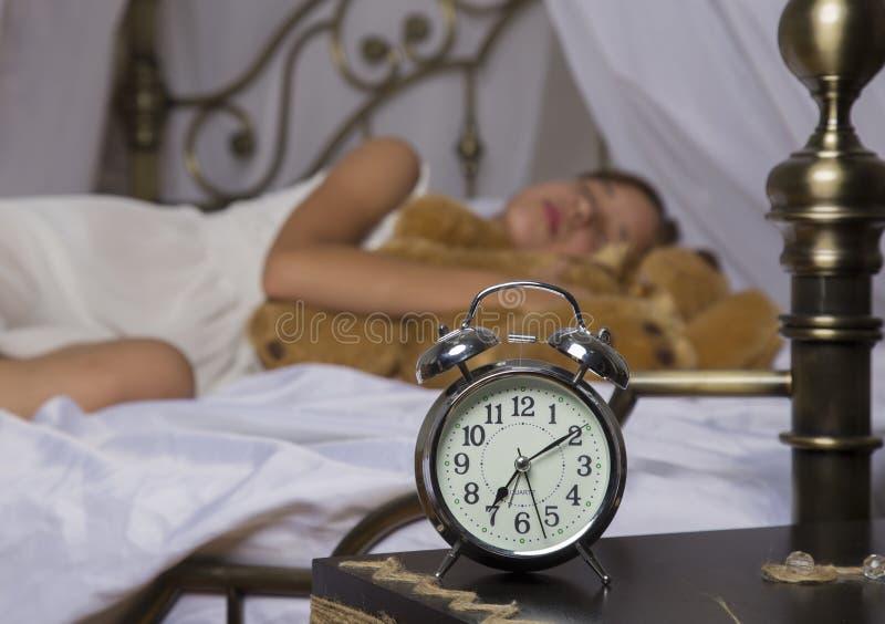 Früh weckend Wecker, der auf Nachttisch steht Wachen Sie von einem schlafenden jungen Mädchen auf, das Teddybären im Bett auf a h lizenzfreie stockfotos