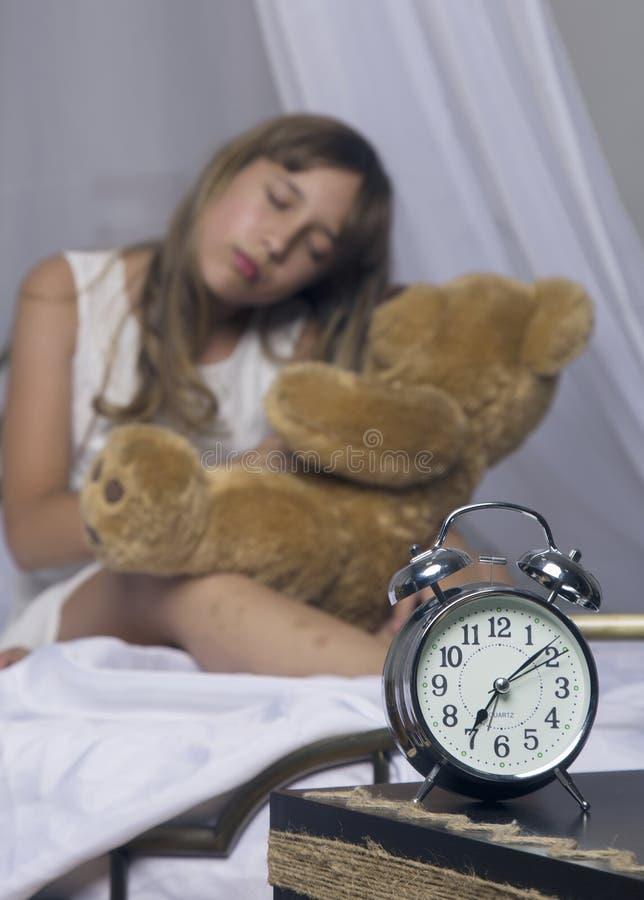Früh weckend Wecker, der auf Nachttisch steht Wachen Sie von einem schlafenden jungen Mädchen auf, das Teddybären im Bett auf a h lizenzfreies stockbild