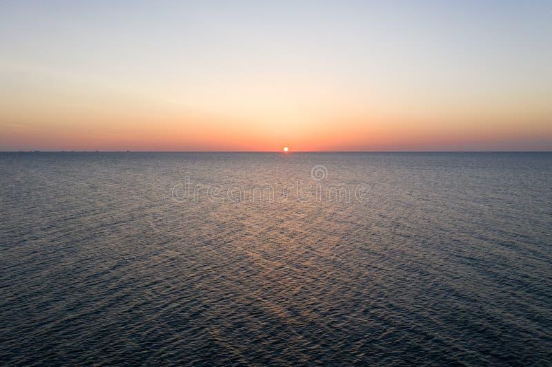 Früher Morgen des Seesonnenaufgangs Schattenbild des kauernden Gesch?ftsmannes Sonnenuntergang Schwarzen Meers Orange Himmel und  lizenzfreies stockbild