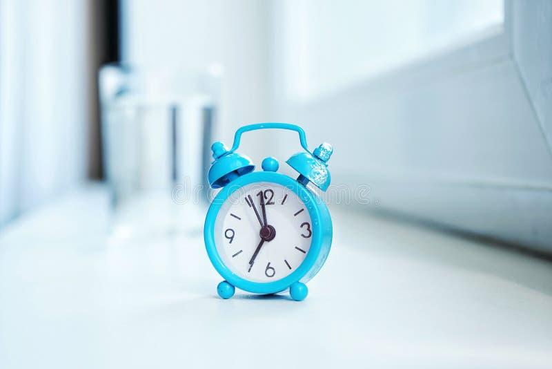 früher Morgen, ein kleiner blauer Wecker mit einer Skala, die morgens sieben, ein Glas Wasser im Hintergrund zeigt stockfotos